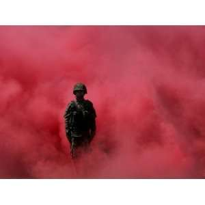 Amidst Smoke from a Flare, a Soldier Attends a Military Ceremony in